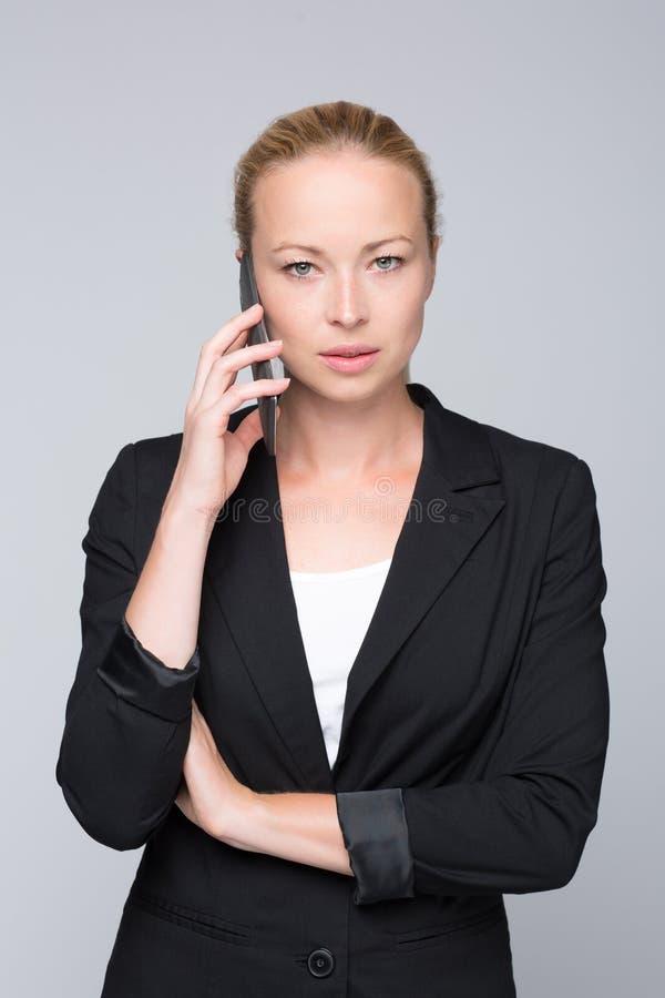 Mooie jonge Kaukasische onderneemster die op mobiele telefoon spreken stock afbeelding