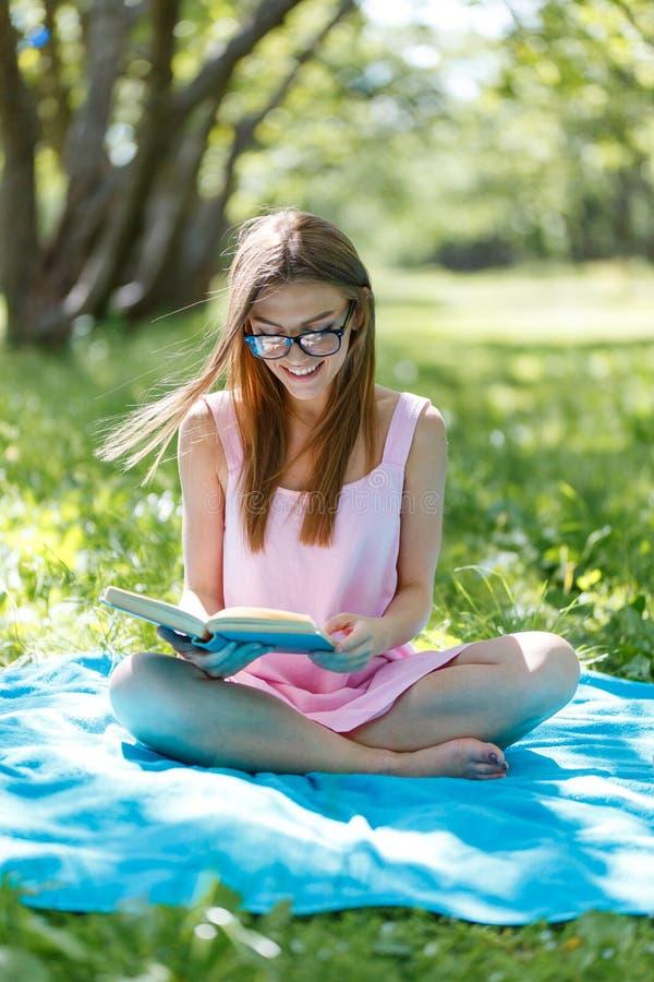 Mooie jonge Kaukasische vrouw die een boek lezen openlucht Het zitten op gras royalty-vrije stock foto