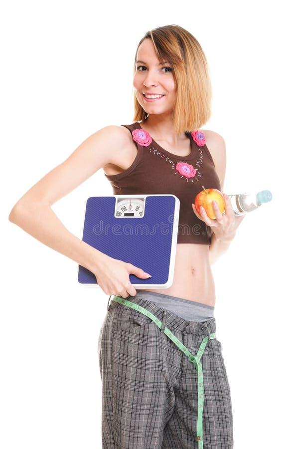 Mooie jonge Kaukasische vrouw die haar lichaam met band ISO meten stock foto
