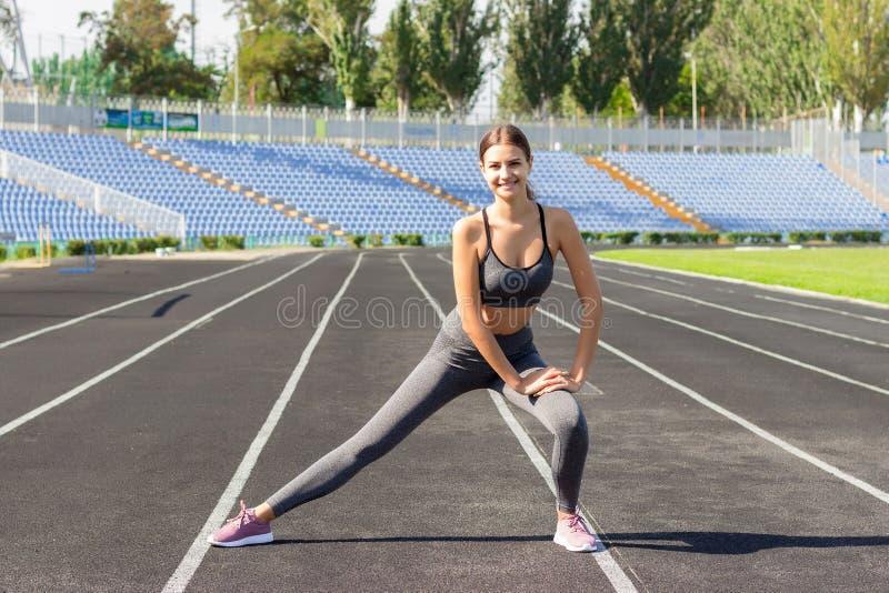 Mooie jonge Kaukasische vrouw die oefeningen doen, opwarmende en uitrekkende opleiding in het runnen van stadion Mensensport en f stock afbeeldingen