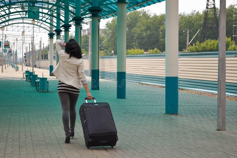 Mooie jonge Kaukasische vrouw die trekkend een bagage bij de post, de zomer, vakantie reizen royalty-vrije stock fotografie