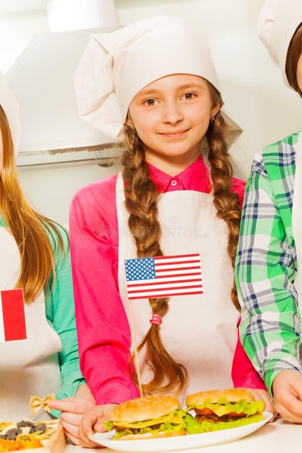 Mooie jonge kok met hamburgers op de plaat royalty-vrije stock foto's