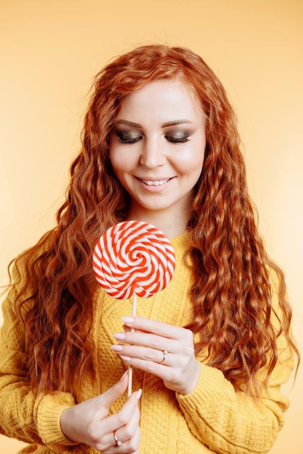 Mooie jonge krullende roodharigevrouw die een rode witte lolly houden stock afbeeldingen