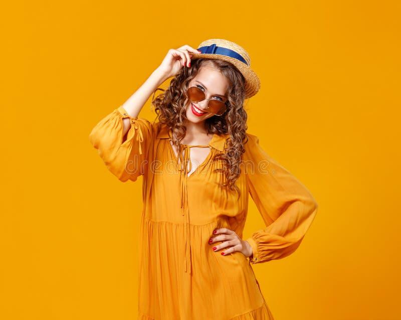 Mooie jonge krullende vrouw in de zomerhoed en zonnebril op gele achtergrond royalty-vrije stock foto's