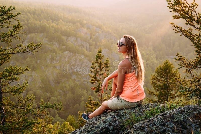 Mooie jonge langharige vrouw die in een t-shirt en borrels op een rots in de bergen in de zomer zitten royalty-vrije stock foto's