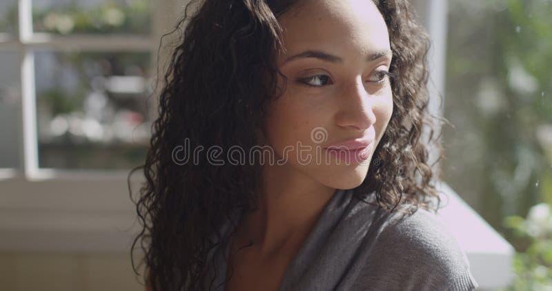 Mooie jonge latino vrouw die uit een venster kijken stock foto