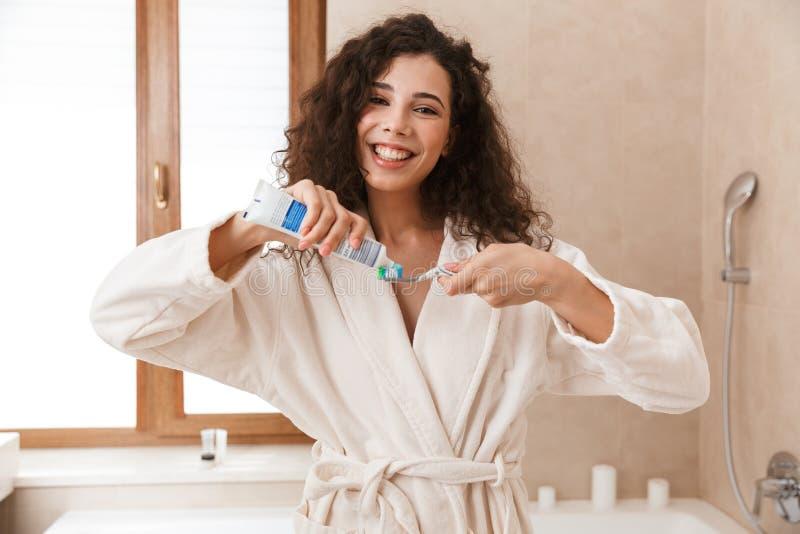 Mooie jonge leuke vrouw die in badkamers schoonmakend haar tanden borstelen stock foto