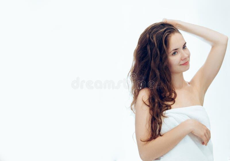 Mooie jonge lotion aanvragen haar en vrouw die terwijl status voor de spiegel in badkamers glimlachen Zorghaar en huid stock fotografie