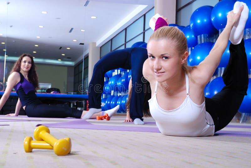 Mooie jonge meisjes die in een gymnastiek uitwerken stock fotografie