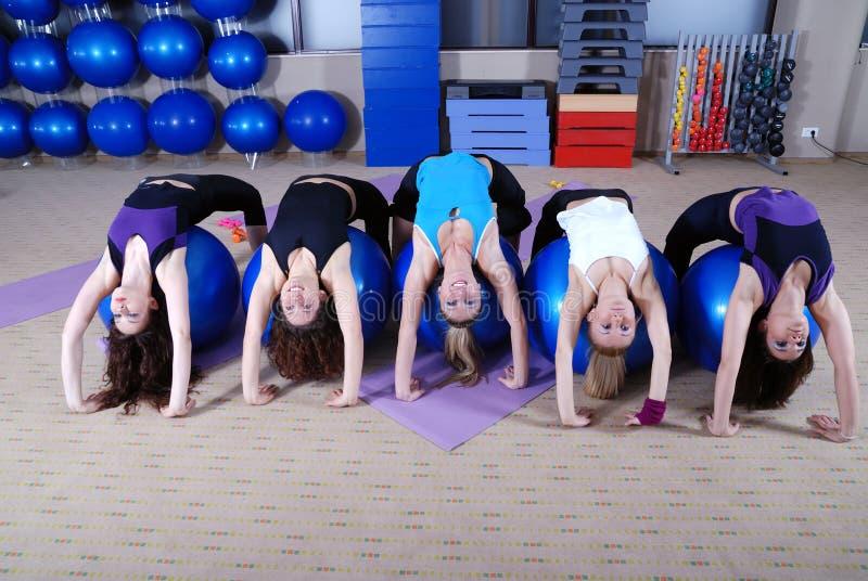 Mooie jonge meisjes die in een gymnastiek uitwerken stock afbeelding