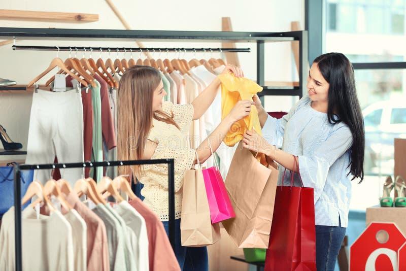 Mooie jonge meisjes die met het winkelen zakken kleren in opslag kiezen stock foto
