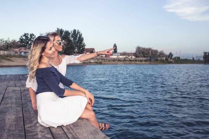 Mooie jonge meisjes die naast rivier genieten van stock foto