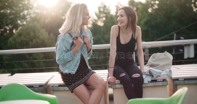 Mooie jonge meisjes die op een dak in een stad ontspannen royalty-vrije stock afbeelding