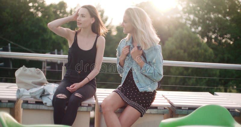 Mooie jonge meisjes die op een dak in een stad ontspannen stock afbeeldingen