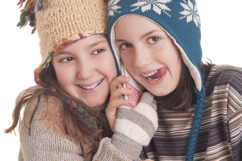 Mooie jonge meisjes die in warme de winterkleren op mobil spreken stock afbeelding