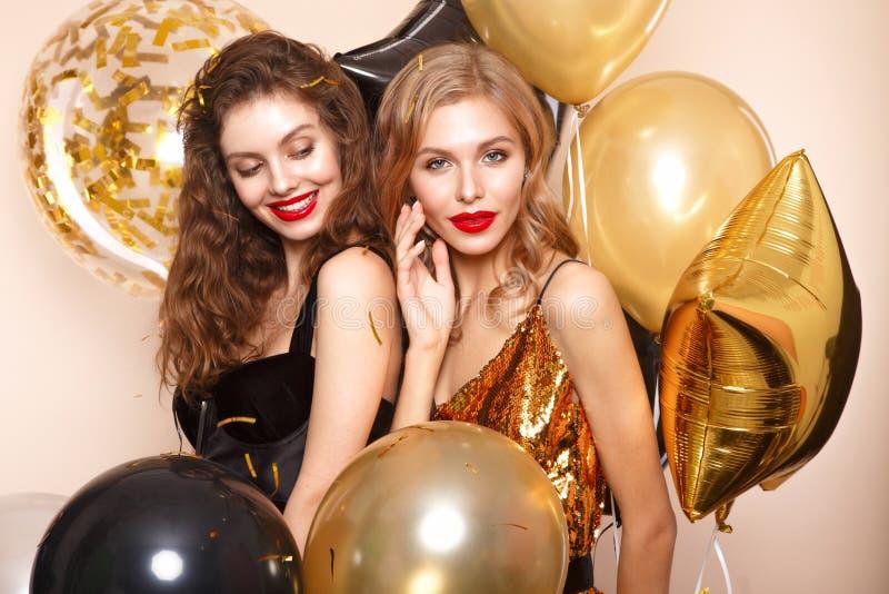 Mooie jonge meisjes in elegante avondjurken met feestelijke ballons Het Gezicht van de schoonheid stock afbeeldingen
