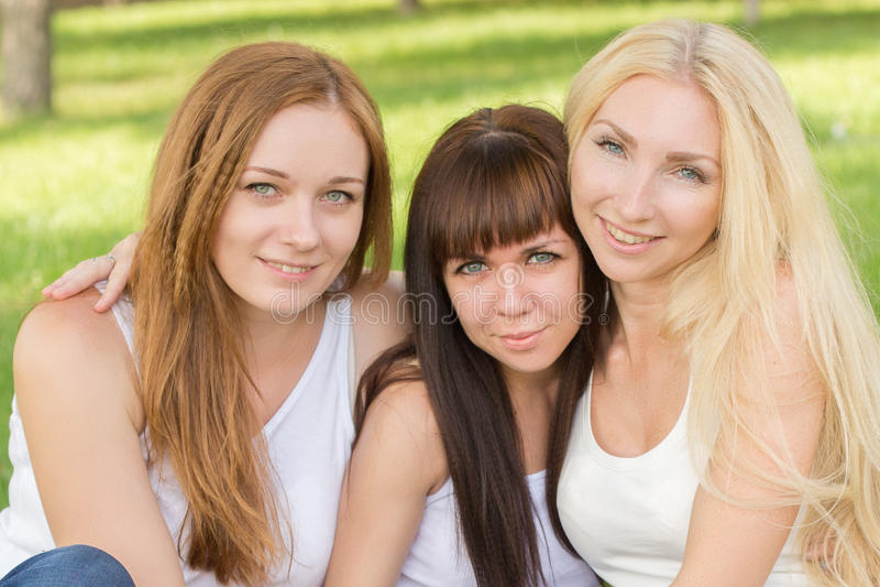 Mooie jonge meisjes stellende zitting op de plaid in het park stock afbeelding