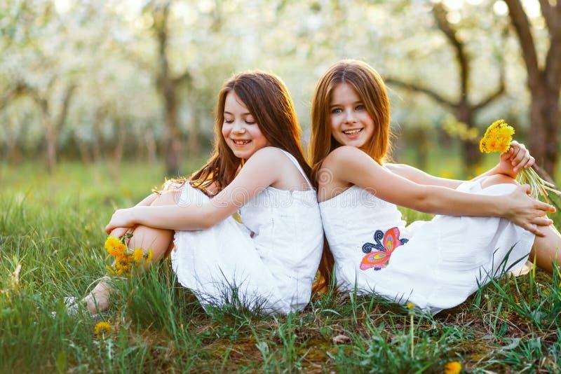 Mooie jonge meisjes in witte kleding in de tuin met appelbomen die bij de zonsondergang blosoming Twee vrienden het koesteren royalty-vrije stock foto's