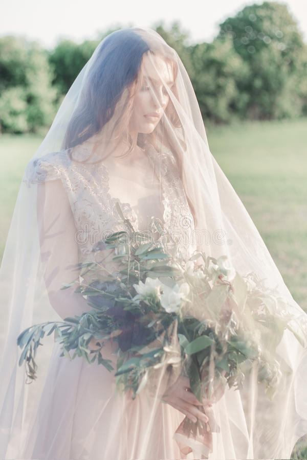 Mooie jonge meisjesbruid in een mooie luchtige kleding in beige kleuren, huwelijk in de stijl van boho stock foto's