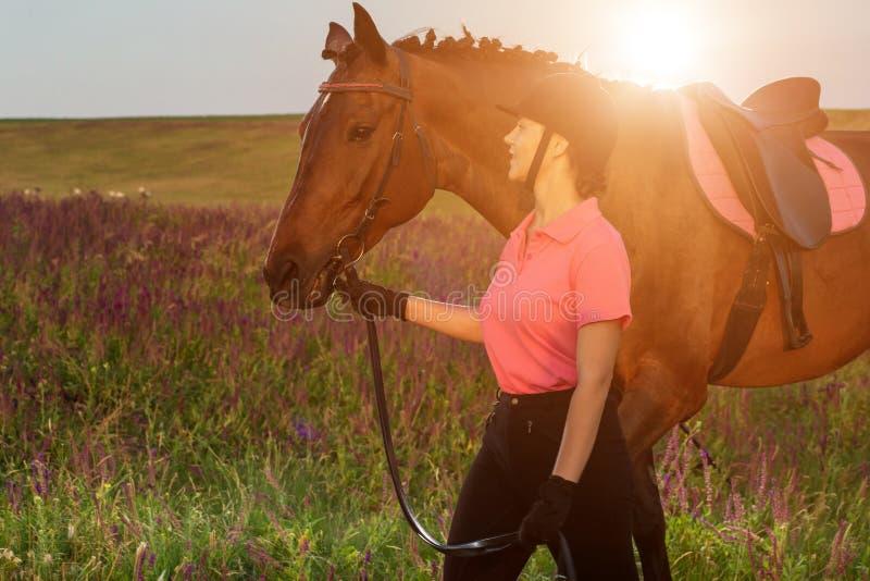 Mooie jonge meisjesglimlach bij haar paard die de eenvormige concurrentie kleden: in openlucht portret op zonsondergang Zongloed stock foto's