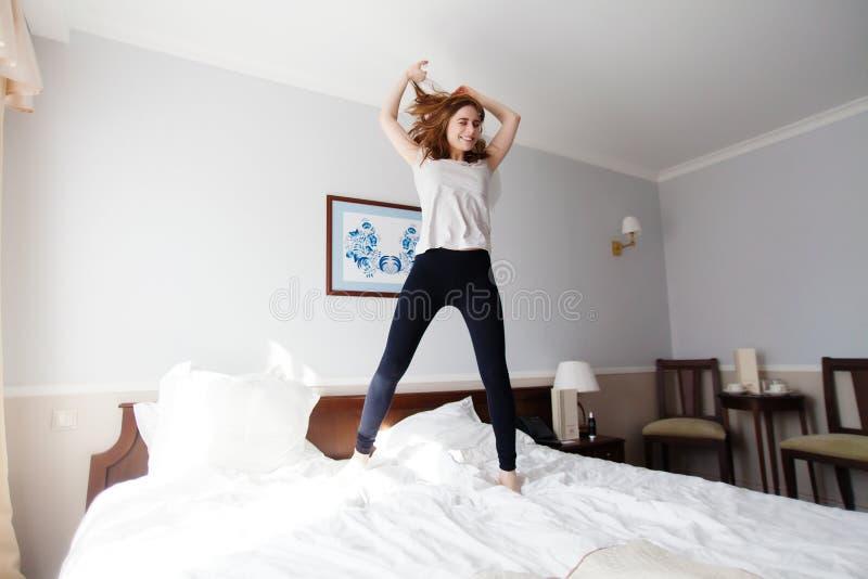Mooie jonge meisjessprongen grappig op tweepersoonsbed in hotel royalty-vrije stock foto's