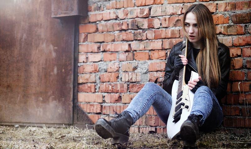 Mooie jonge meisjestuimelschakelaar met elektrische gitaar Een rotsmusicia royalty-vrije stock afbeelding