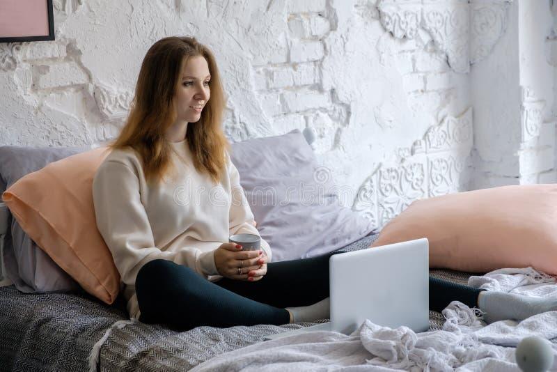 Mooie jonge meisjeszitting in de ochtend in bed, het drinken zwarte koffie en het kijken met rente in het laptop boek stock afbeelding