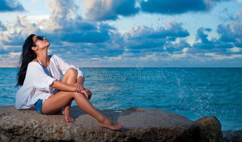 Mooie jonge meisjeszitting door de oceaan die van de zonsondergang genieten royalty-vrije stock foto's