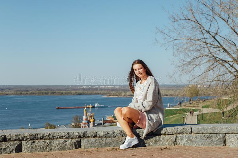 Mooie jonge meisjeszitting op de Volga rivierdijk royalty-vrije stock afbeelding