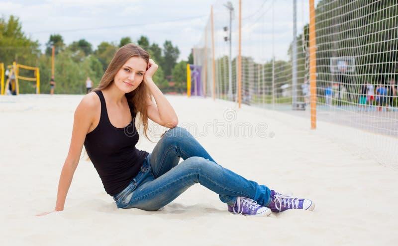 Mooie jonge meisjeszitting op het zand nex aan het net voor volleyball van Zonnige warme dag royalty-vrije stock fotografie