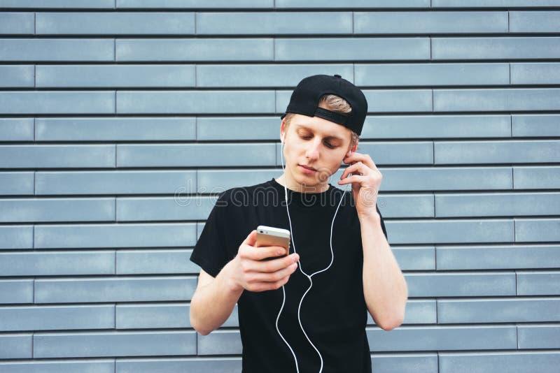 Mooie jonge mens in een GLB en een zwart overhemd die aan muziek op hoofdtelefoons met uw telefoon luisteren royalty-vrije stock afbeeldingen