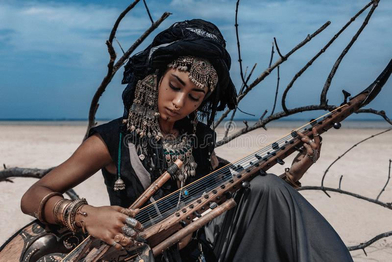 Mooie jonge modieuze stammenvrouw in het oosterse kostuum spelen royalty-vrije stock afbeelding