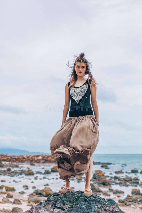 Mooie jonge modieuze vrouw die in roze rok op het strand lopen stock foto's