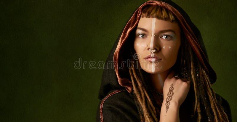 Mooie, jonge, modieuze vrouw met dreadlocks in een zwart, stammenkostuum op groene achtergrond stock afbeelding