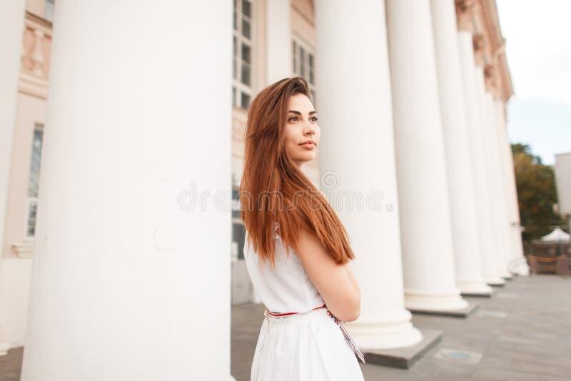 Mooie jonge modieuze vrouw in in witte kleding die dichtbij stellen stock foto's