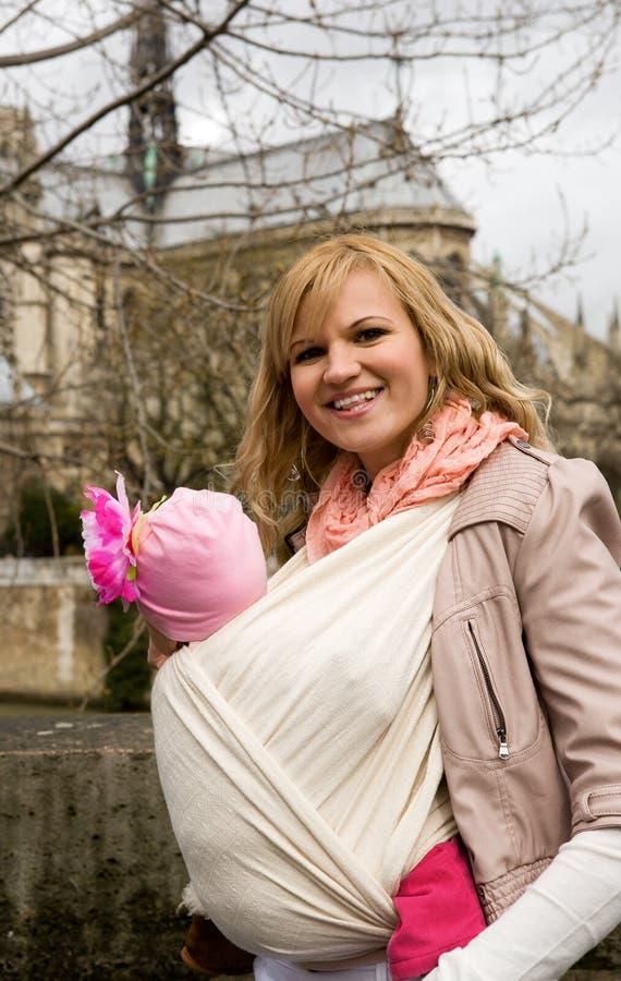 Mooie jonge moeder die haar baby in slinger vervoert stock foto's