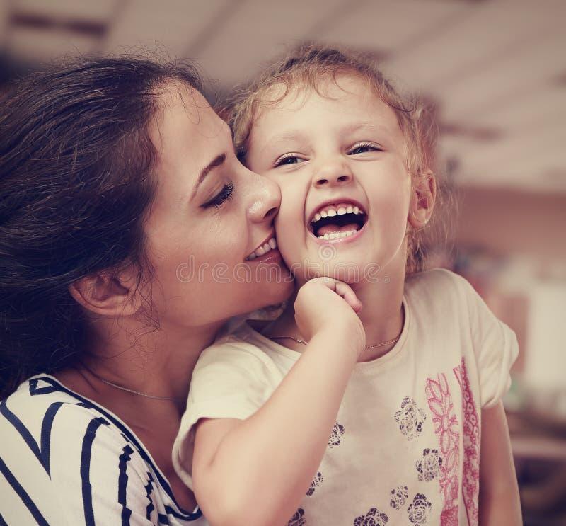 Mooie jonge moeder die haar joying gelukkige leuke dochter kussen stock foto
