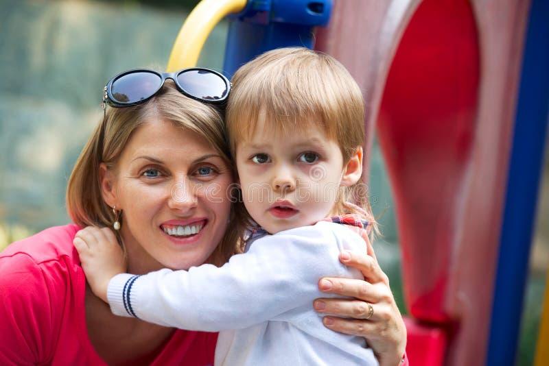 Mooie jonge moeder die haar leuke zoon koesteren royalty-vrije stock afbeeldingen