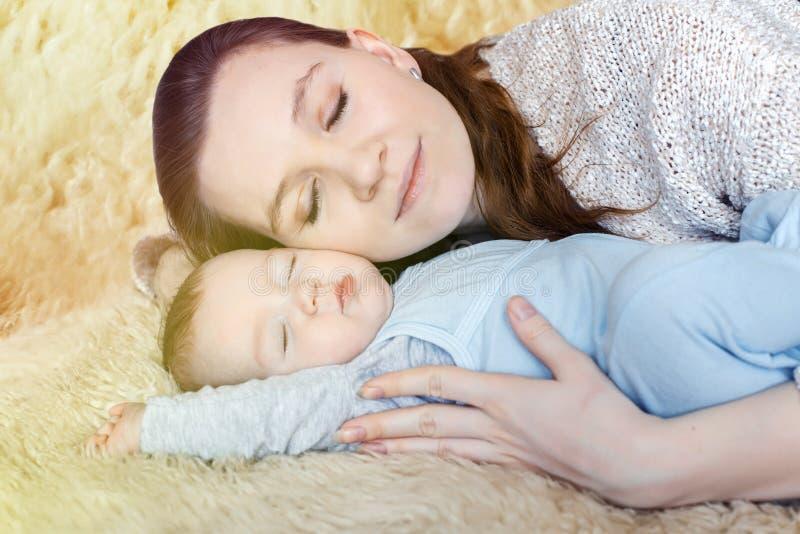 Mooie, jonge moeder die haar slaapbaby koesteren royalty-vrije stock afbeeldingen
