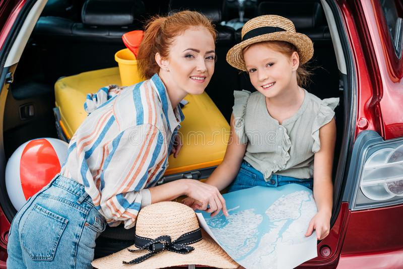 mooie jonge moeder en dochter in klaar autoboomstam stock fotografie