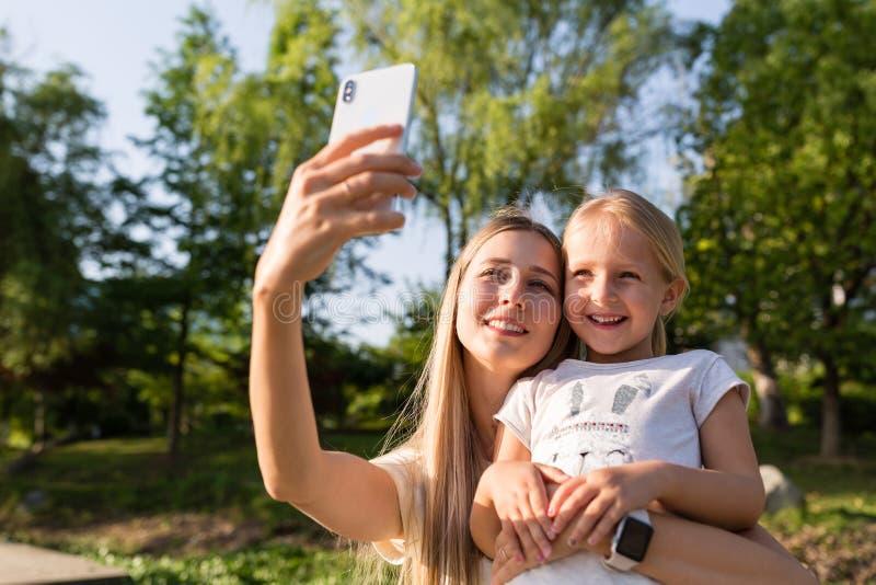 Mooie jonge moeder en dochter met blondehaar dat mobiele telefoon met behulp van openlucht Modieuze meisjes die selfie in het par royalty-vrije stock afbeeldingen
