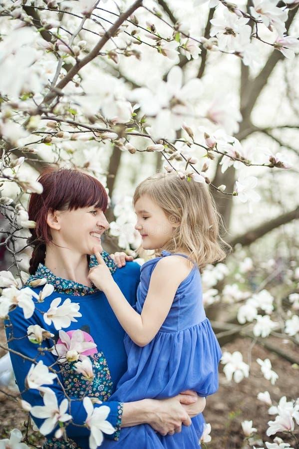 mooie jonge moeder met babymeisje in haar wapens Het concept een gelukkige familie, moederschap moeder met haar dauther met bloem stock foto