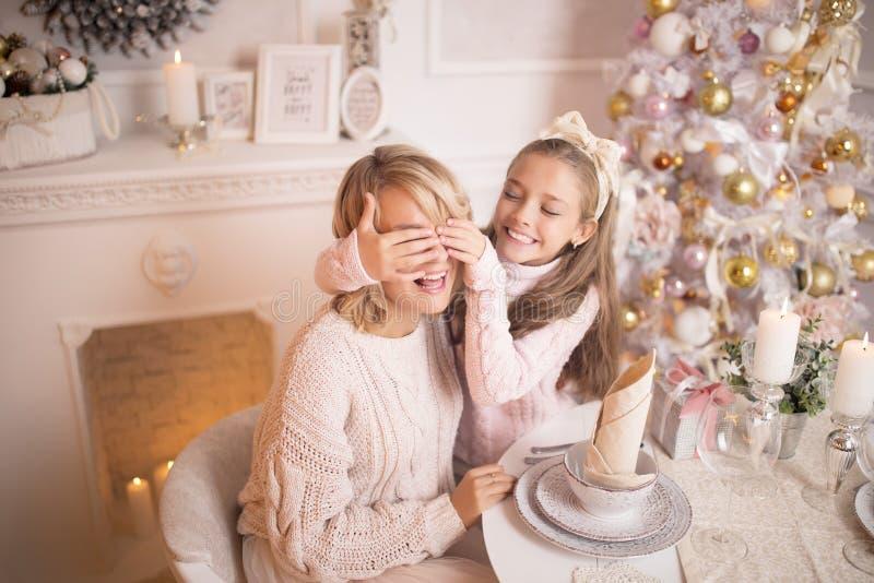 Mooie jonge moeder met haar dochter in het binnenland van het Nieuwjaar bij de lijst dichtbij de Kerstboom royalty-vrije stock foto's