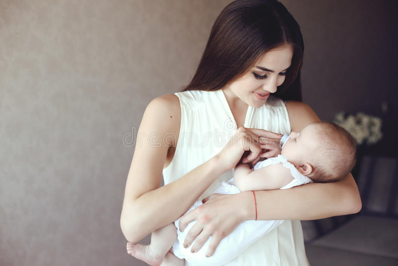 Mooie jonge moeder met lang donker haar die met haar weinig aanbiddelijke baby stellen stock foto