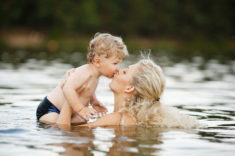 Mooie jonge moeder met zoon in water stock afbeeldingen