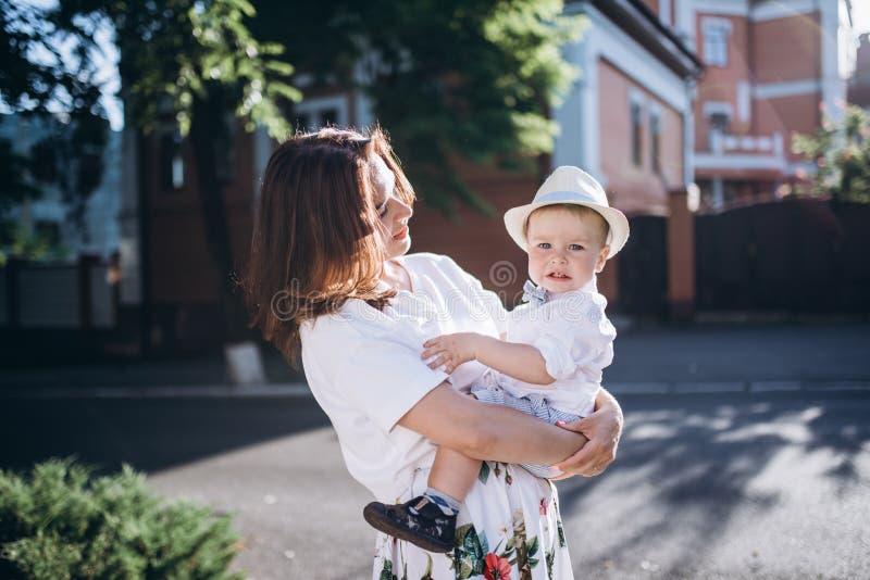 Mooie jonge momhold hun zoon De vrouw kijkt aan de zoon, zijn zij allebei voelen gelukkig stock foto's