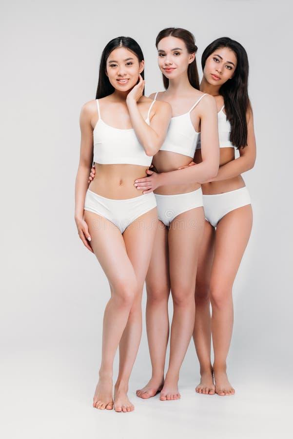 mooie jonge multi-etnische vrouwen die in witte lingerie koesteren royalty-vrije stock foto
