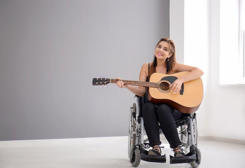 Mooie jonge musicus in rolstoel het spelen gitaar binnen royalty-vrije stock afbeelding