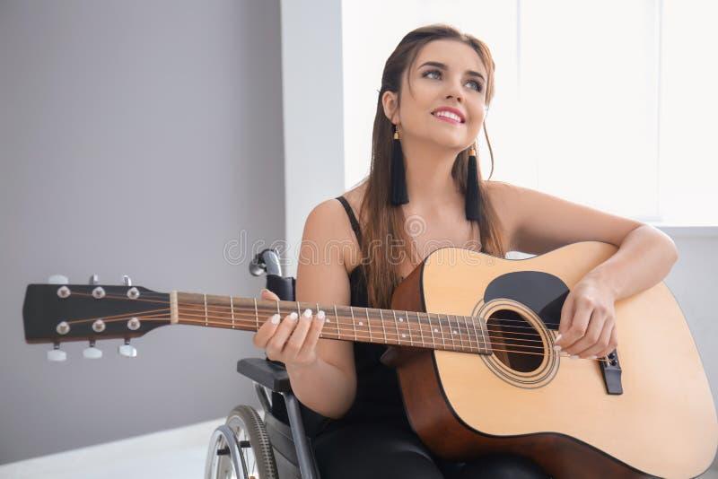 Mooie jonge musicus in rolstoel het spelen gitaar binnen royalty-vrije stock foto