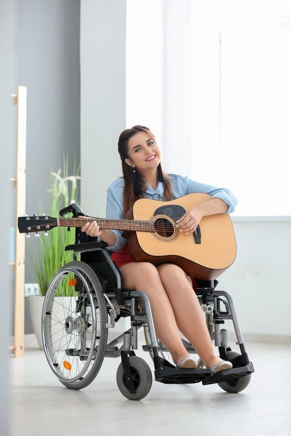 Mooie jonge musicus in rolstoel het spelen gitaar thuis royalty-vrije stock afbeeldingen